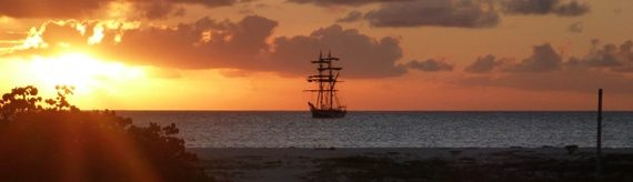 tall ship on the horizon during sunset